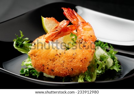Deep fried shrimps with lettuce on black plate