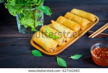 deep fried spring rolls in wooden tray with sauce place on black table