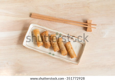 Deep fried spring rolls with pork stuffed serve on wood table that found in East Asian and Southeast Asian cuisine. - stock photo