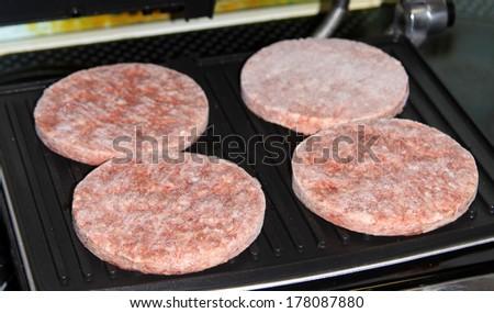 Deep-frozen hamburgers on the grill - stock photo