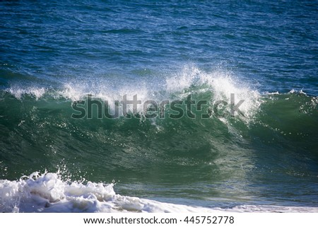 Deep green waves with white frothy crests  from the Indian Ocean are about to break on the basalt rocks at Ocean Beach Bunbury South Western Australia in early winter.