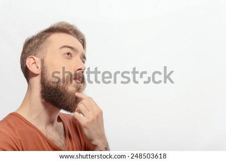 Deep in thoughts. Young bearded man touching his chin with a finger looking at copy space while standing against white background - stock photo