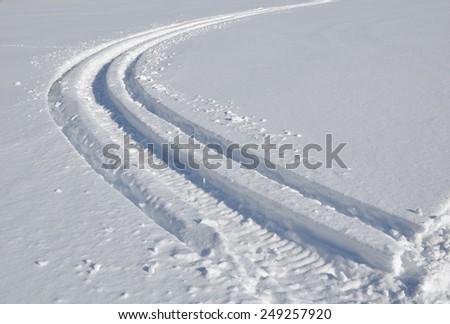 Deep markings of snowmobile in a frozen lake - stock photo