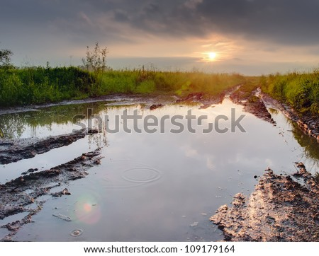 Deep puddle on a dirty road - stock photo
