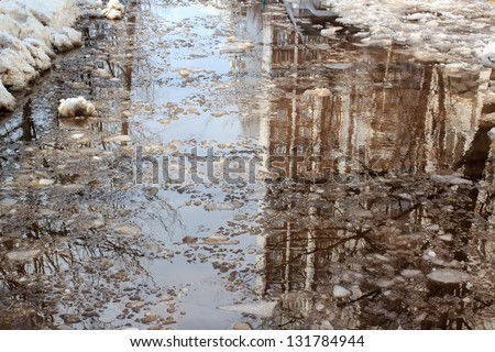 Deep puddle with lumps snow melts on the road in the city, during the melting of snow - stock photo