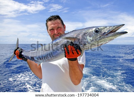 Deep sea fishing. Fisherman holding a wahoo fish. - stock photo