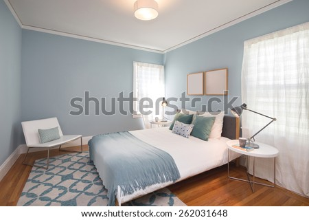 Deep Turquoise Blue bedroom with matching decoration and white leather chair.  - stock photo