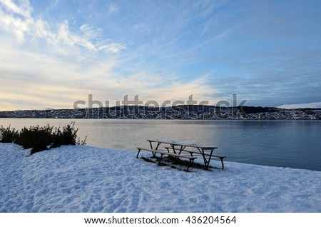deep vibrant winter sky with snowy sea shore and the tromsoe city island in the background in northern Norway - stock photo
