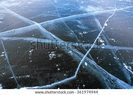 Deep wide cracks in the dark blue frozen water of the sea bay - stock photo