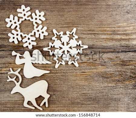 Deer, angel and snowflake shape made of wood on wooden table. Christmas decor. - stock photo