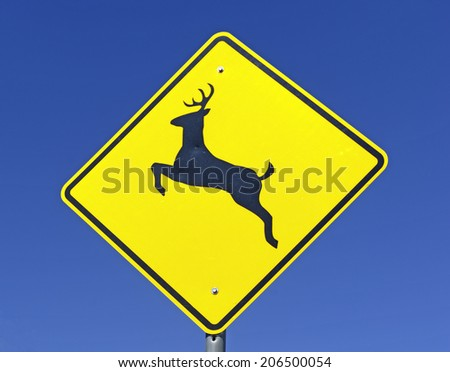 Deer Crossing warning sign on road - stock photo
