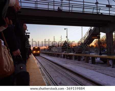 Deer Park, NY - January 26, 2016: Commuters on Long Island await an approaching LIRR train on the platform returning to work after Blizzard Jonas shut down parts of the area. - stock photo