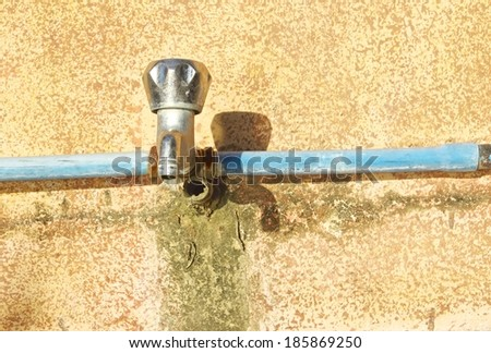Defective faucet on an old wall. Cause wastage of water. - stock photo