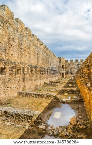 Defence tower and battlements of the ancient  Venetian fortress Frangokastello.Destroyed buildings of the inner yard.District of Chania. Crete island. Greece.Europe.  - stock photo