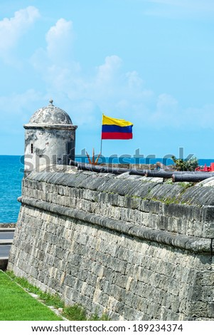 Defensive wall of Cartagena with a Colombian flag waving and several cannons visible in the old town of Cartagena, Colombia - stock photo