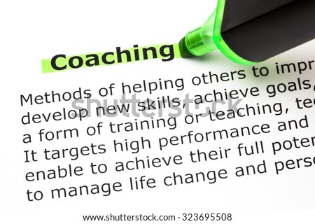 Definition of the word Coaching printed on paper and highlighted with green text marker. - stock photo