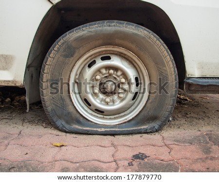 Deflated damaged tyre on car wheel. - stock photo