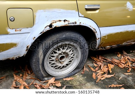 Deflated damaged tyre on white car wheel - stock photo