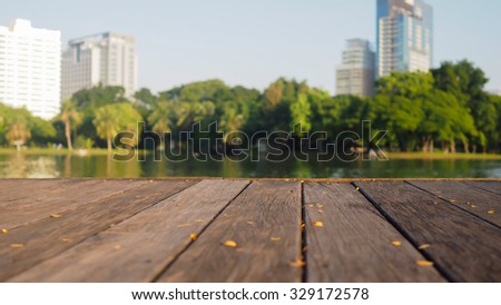 Defocus and blur image of terrace wood and water, trees and building inside. Park view in the city, natural background