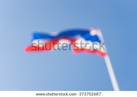 Defocus Image of waving Thai flag of Thailand with blue sky background.