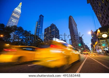 Defocus motion blur view of yellow taxis driving through the city streets at dusk in New York City, USA. Slow shutter speed to enhance motion blur effect.