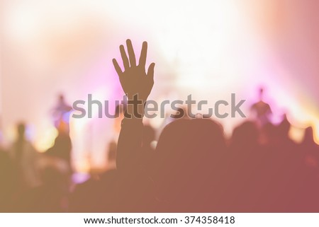 defocus of christian music concert with raised hand - stock photo