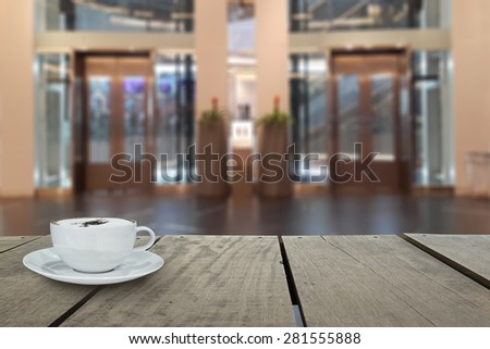 Defocus with terrace wood and cappuccino coffee with elevators in shopping mall for background usage - stock photo