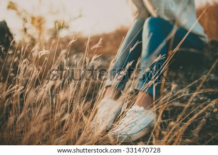 Defocused abstract loneliness concept. Cropped feet of lonely young woman sitting on stone. Solitude - stock photo