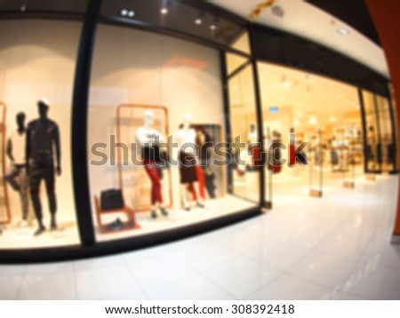 Defocused and blur image of a large shopping mall hall with glass display cases and mannequins with wide angle fisheye lens and distortion view. The image was blurry for use as background - stock photo