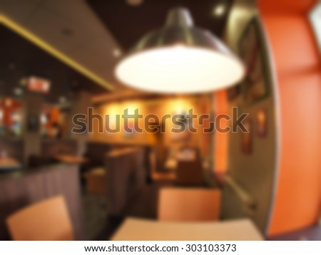 Defocused and blur interior of the restaurant with a bright lamp in the foreground. The image was blurred for use as a background.