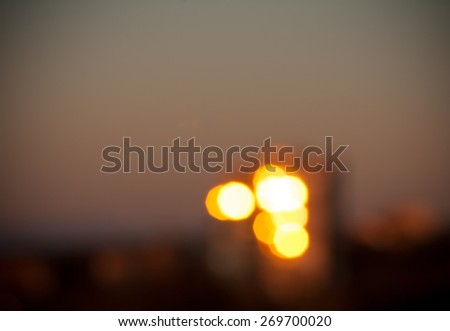 Defocused and blurred abstract glitter spherical glow lights bokeh background of gold and black vivid color with vignette effect at the image corners, capturing setting sun rays reflections in windows - stock photo