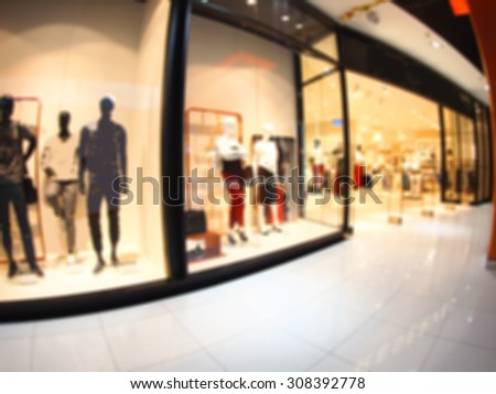 Defocused and blurred image of a large shopping mall hall with glass display cases and mannequins with wide angle fisheye lens and distortion view. The image was blurry for use as background - stock photo