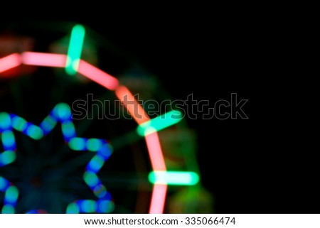 Defocused and blurred image of ferris wheel in the amusement park at night for background usage. - stock photo