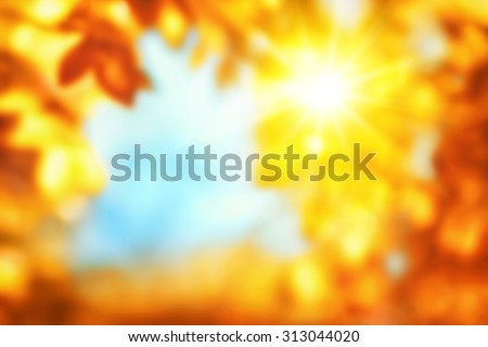 Defocused autumn background with shiny vivid happy colors showing the sun shining through gold and red leaves, framing blue sky - stock photo