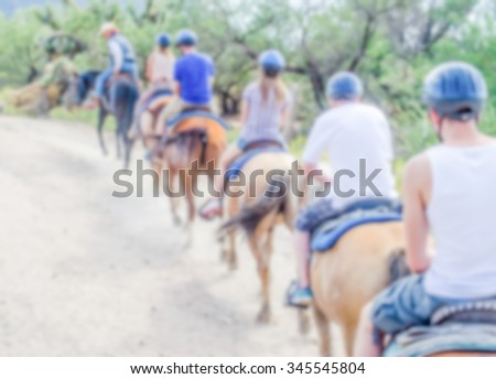 Defocused background of a group of horse riders. Intentionally blurred post production for bokeh effect - stock photo