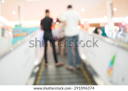 Defocused Background of People Using Escalator in Shopping Mall - stock photo