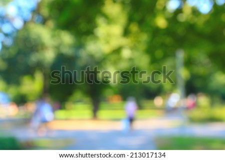 Defocused background of summer park with walking people - stock photo