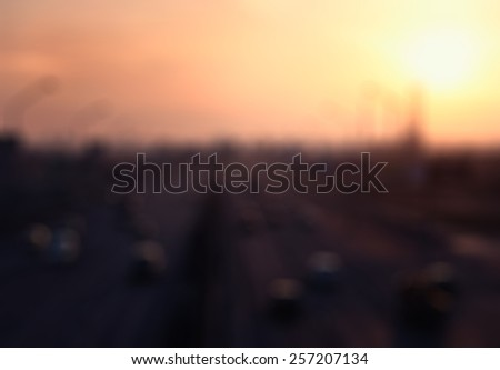 defocused background of sunset highway road with cars - stock photo