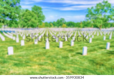 Defocused background with rows of white grave stones in cemetery. Intentionally blurred post production for bokeh effect - stock photo