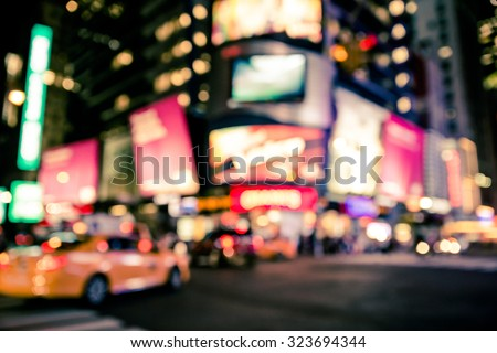 Defocused blur of New York City lights in Times Square with taxicab and cars