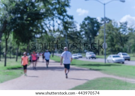 Defocused, blurred motion background of summer activities with energetic people jogging, walking, running and bicycling at green city park. Urban outdoor workout.Healthy lifestyle concept.Vintage look - stock photo