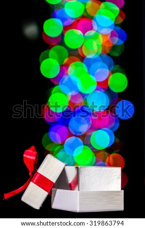 Defocused bokeh lights are moving out of open gift box - stock photo