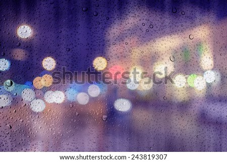 defocused bokeh lights at Phuket old town view past glass and drop water