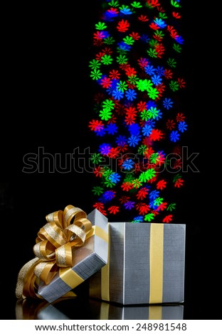 Defocused bokeh lights flower shaped are moving out of open gift box - stock photo