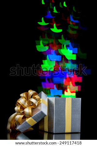 Defocused bokeh lights thumbs up shaped are moving out of open gift box - stock photo
