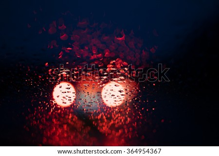 Defocused car lights in a city center with rainwater reflections on the windscreens at night