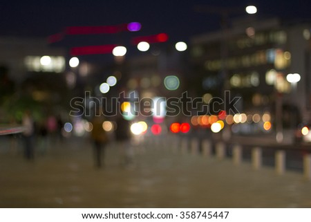 Defocused city lights in the background with blurring lights ,people and traffic