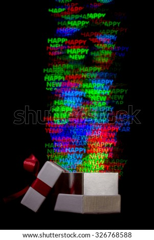 Defocused happy new year word lights are moving out of open gift box - stock photo
