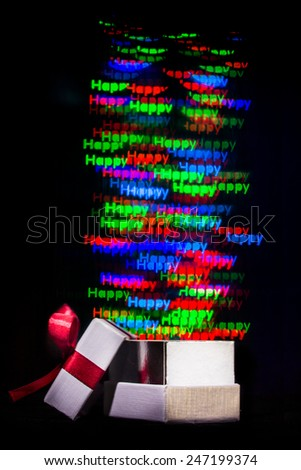 Defocused happy word lights are moving out of open gift box - stock photo
