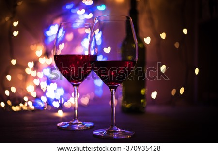 Defocused heart shaped lights bokeh and glasses of wine. Valentine Day concept. Copy space for your text (Dark background)